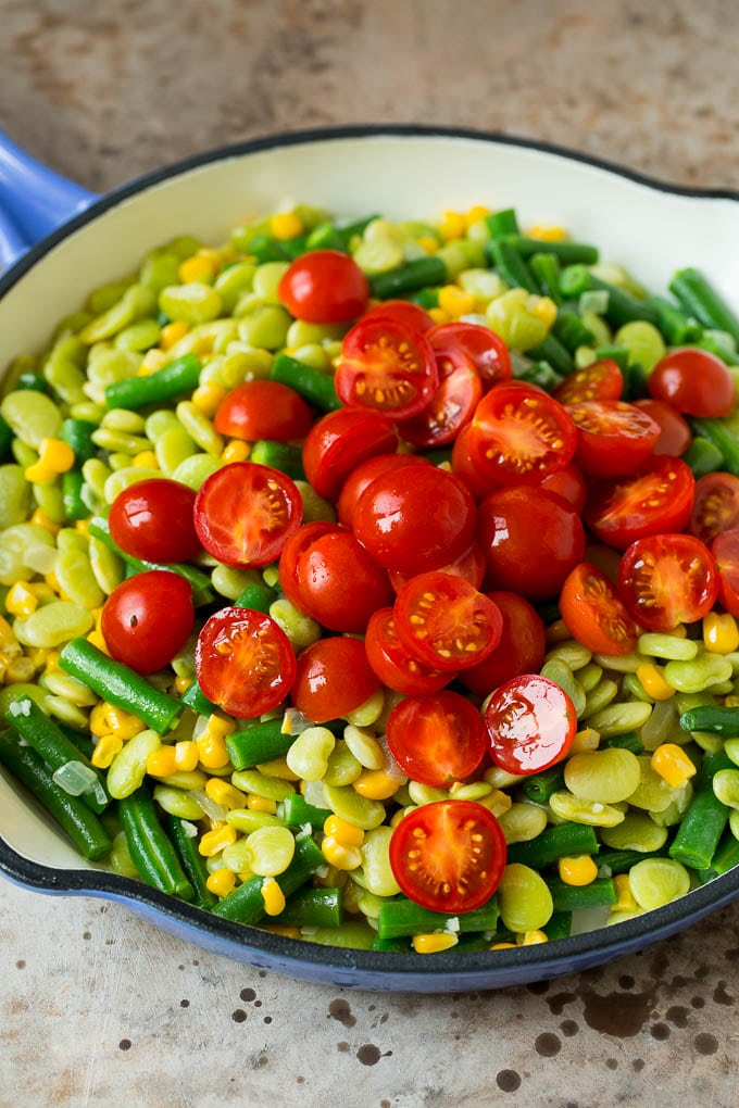 A pile of cherry tomatoes on top of a mixture of corn and beans.
