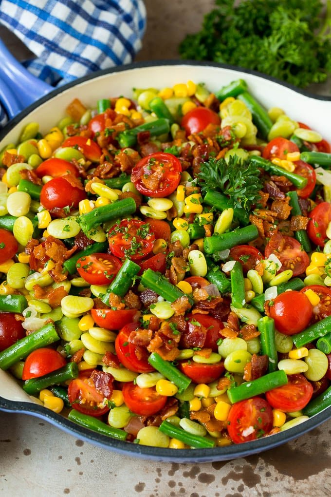A skillet of succotash topped with bacon and herbs.