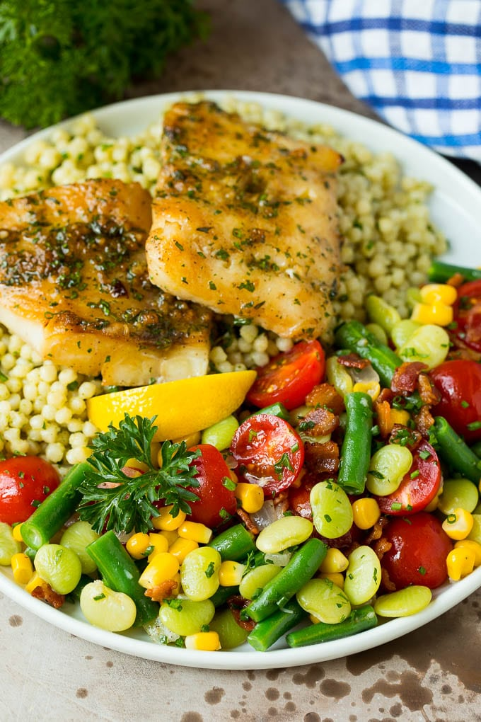 Succotash served on a plate with fish and couscous.