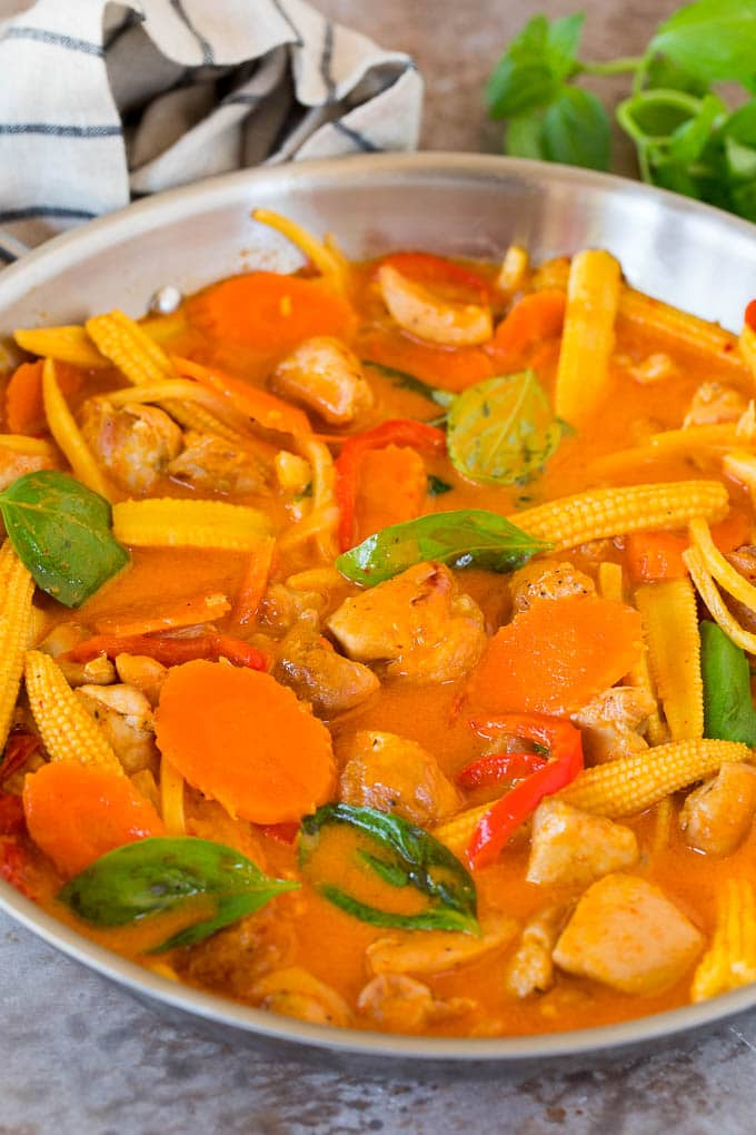 A pan of Thai chicken curry in a creamy red sauce with vegetables.