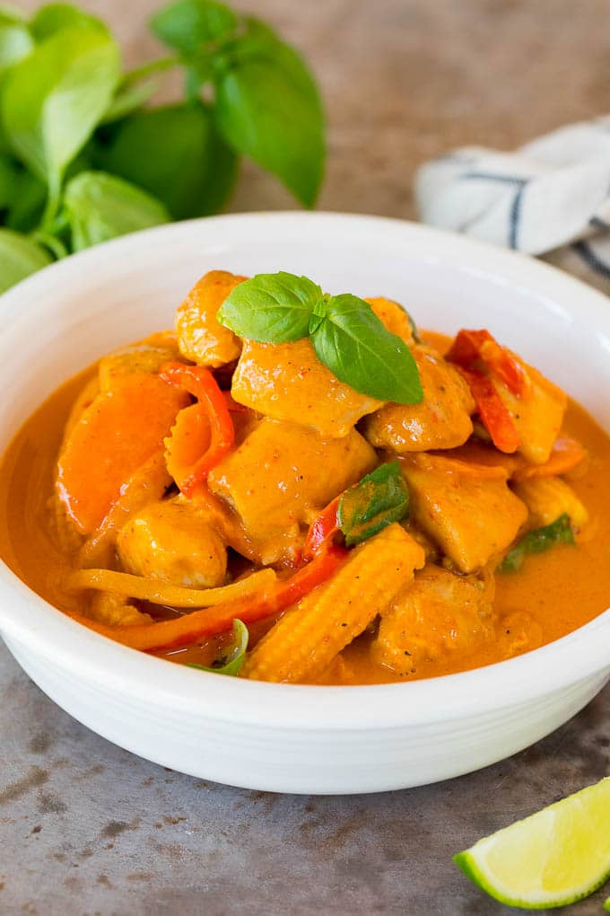 A bowl of Thai chicken curry topped with fresh basil.