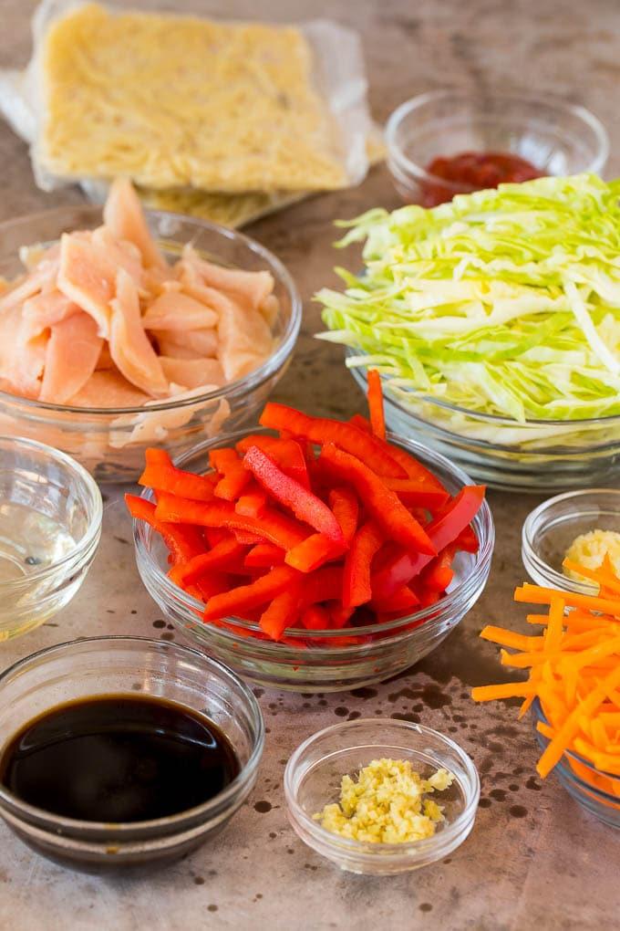 Bowls of shredded vegetables, sliced chicken and seasonings.