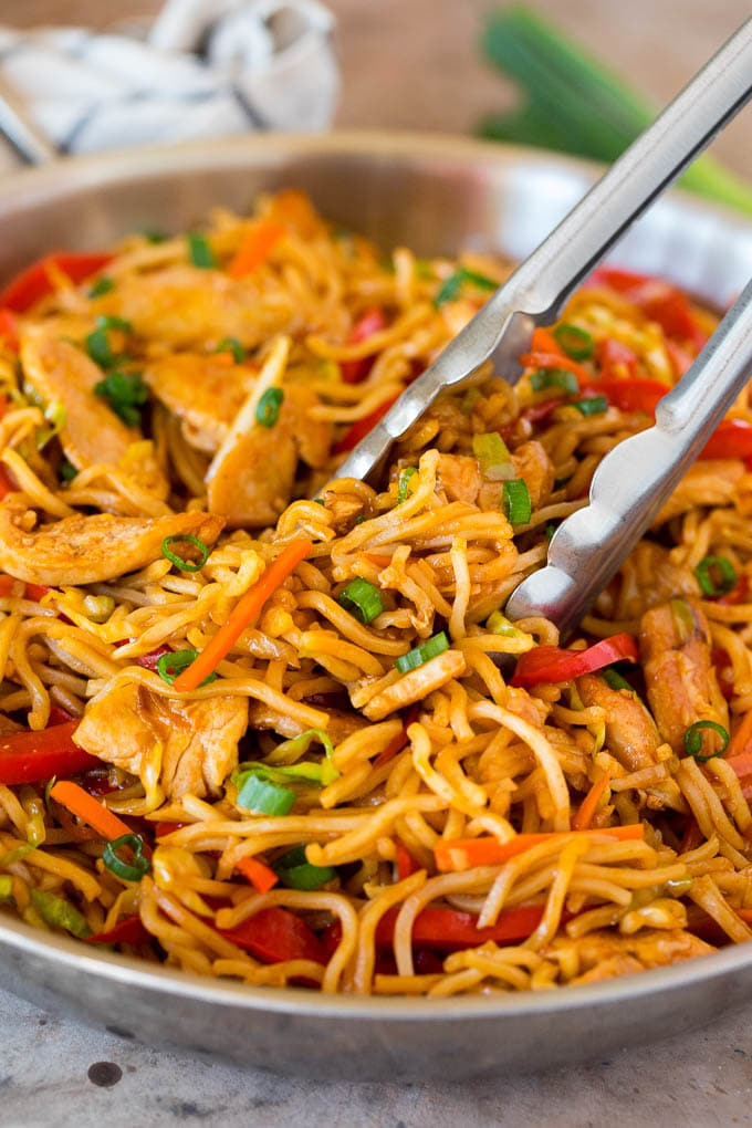 Tongs serving up a portion of yakisoba noodles with vegetables and chicken.