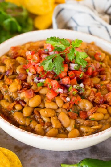 A bowl of charro beans topped with bacon and pico de gallo.