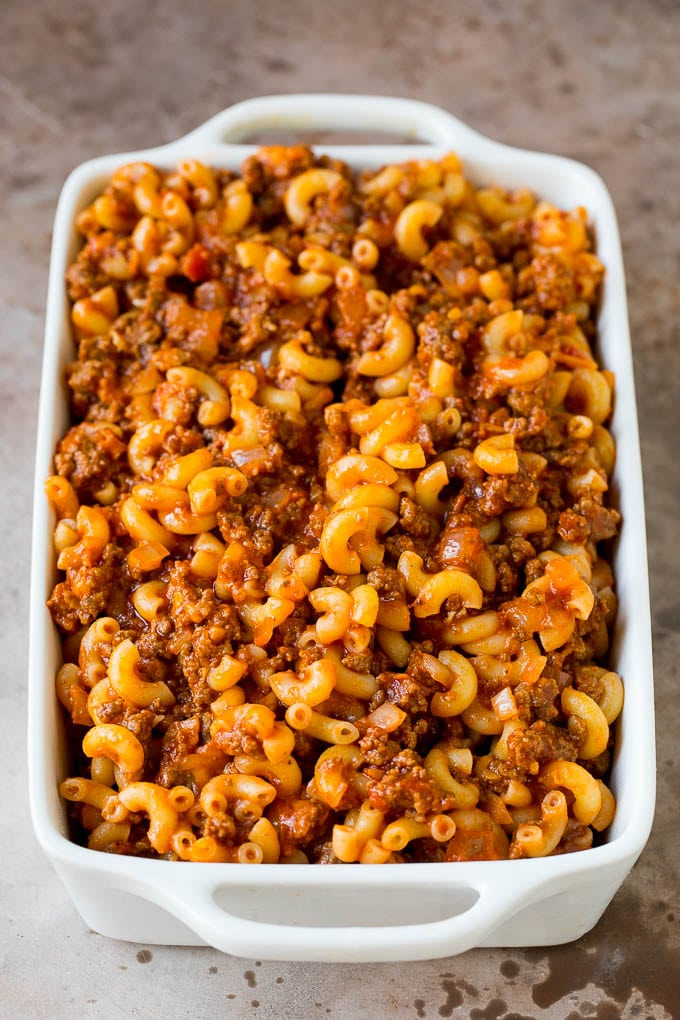 Beef and sauce tossed with macaroni in a baking dish.