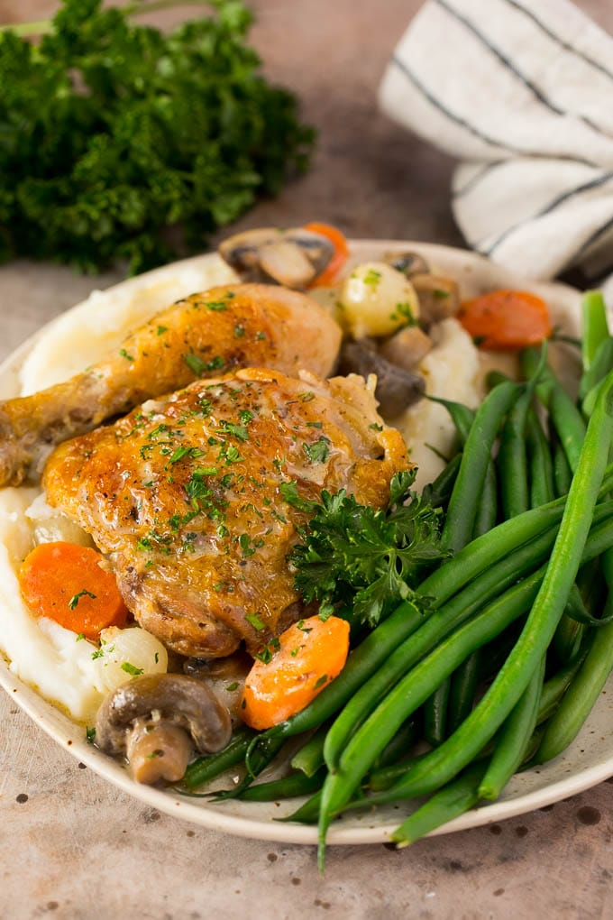 A plate of chicken fricassee served with mashed potatoes and green beans.
