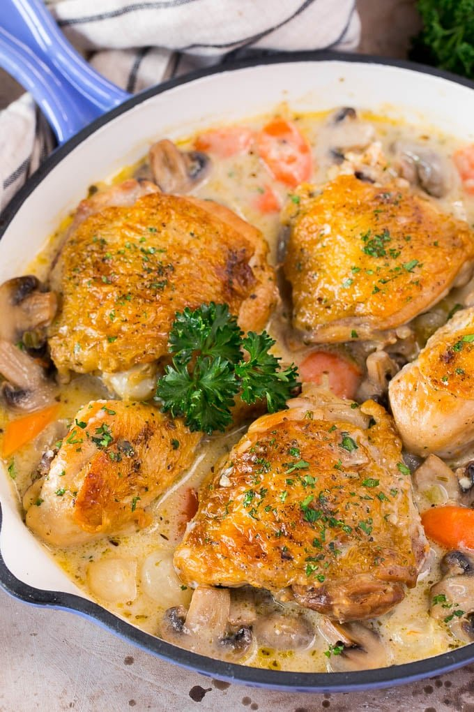 A pan of chicken fricassee in a creamy sauce with vegetables.