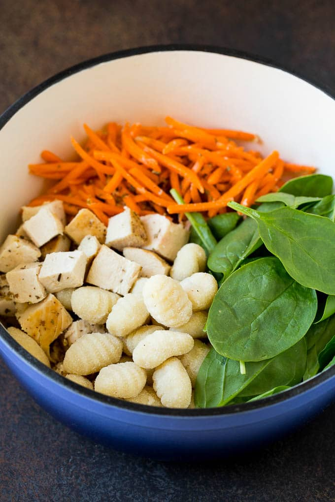 Chicken, spinach, carrots and gnocchi in a pot.