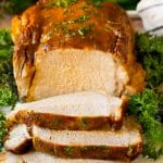 Crock pot pork loin sliced on a serving plate, garnished with herbs.