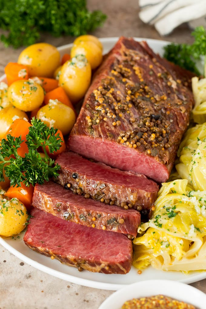 Instant Pot corned beef sliced and served with cabbage, carrots and potatoes.