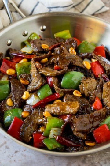 Kung pao beef with peppers and peanuts in a saute pan.