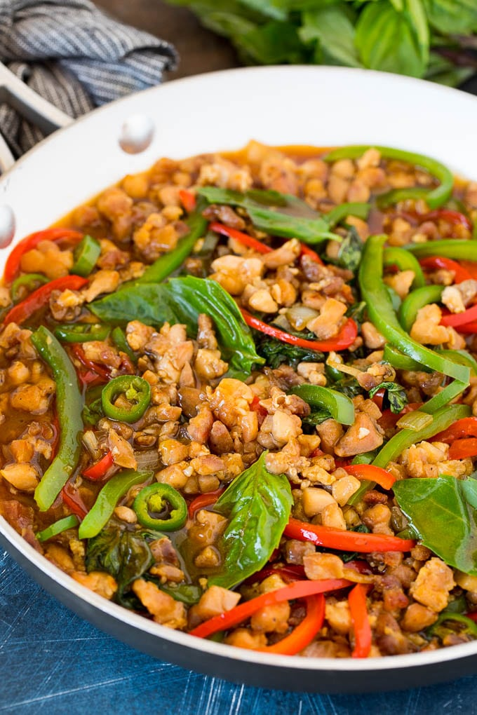 A pan of Thai basil chicken with peppers and fresh basil leaves.