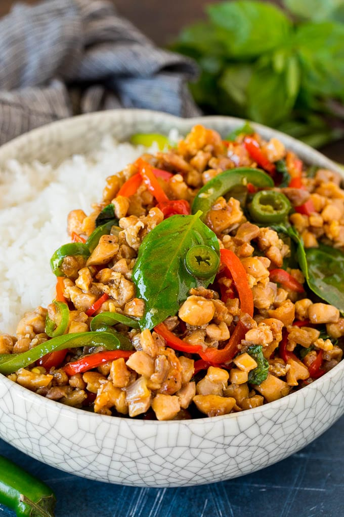 A bowl of Thai basil chicken served over rice.