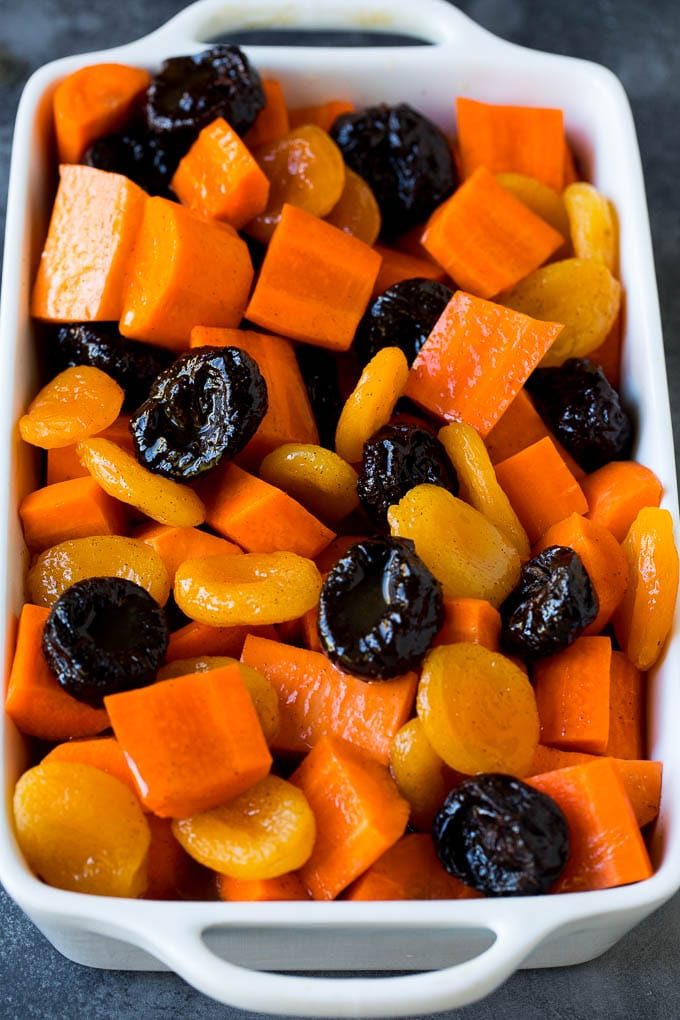 Carrots, sweet potatoes and dried fruit in a baking dish.