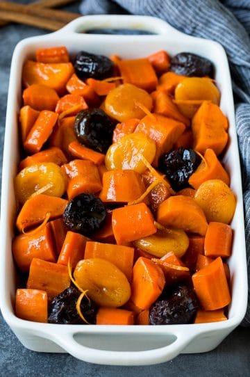 A baking dish of tzimmes garnished with orange zest.