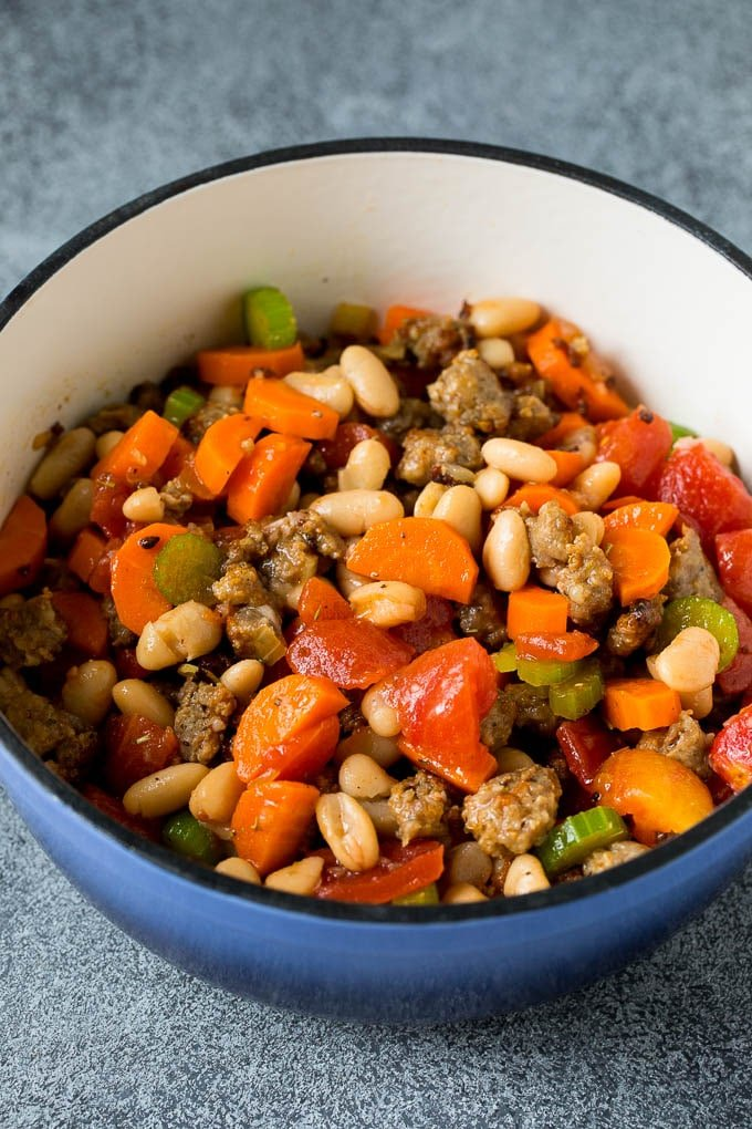 A mixture of beans, tomatoes, vegetables and sausage in a pot.