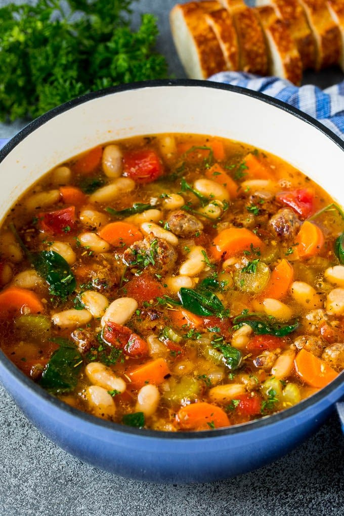 A pot of Tuscan white bean soup with sausage and vegetables.