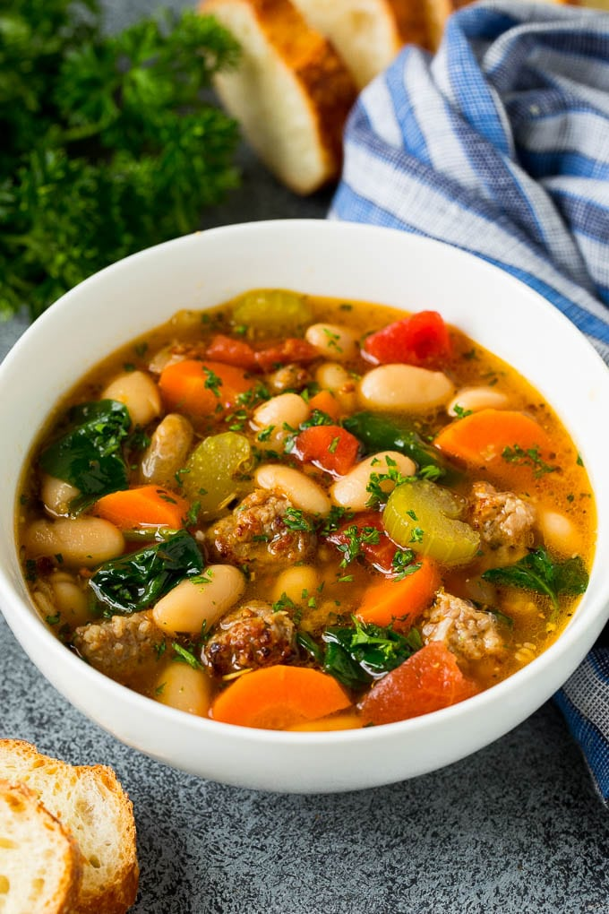 A bowl of white bean soup with Italian sausage, tomatoes and spinach.