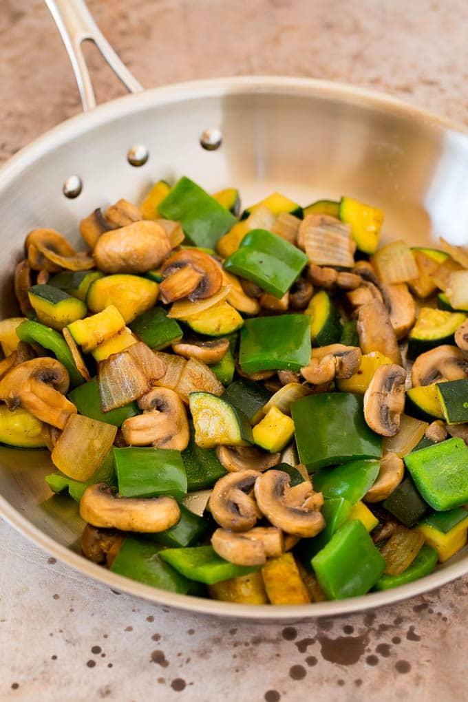 Mushrooms, zucchini and bell peppers cooked in a pan.