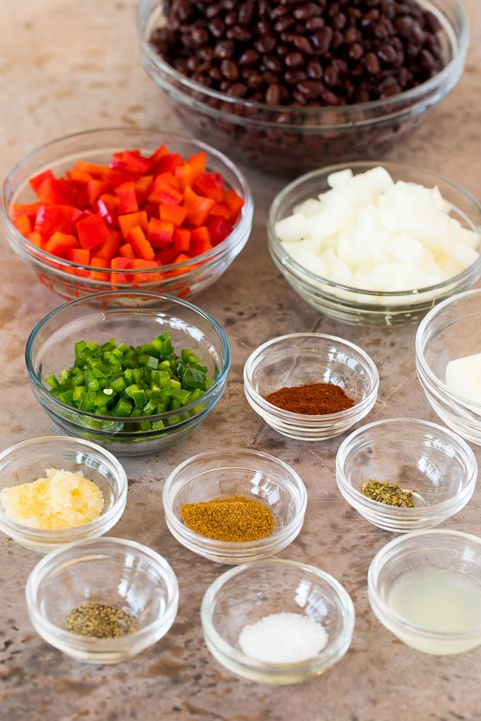 Glass bowls of ingredients including black beans, vegetables and spices.