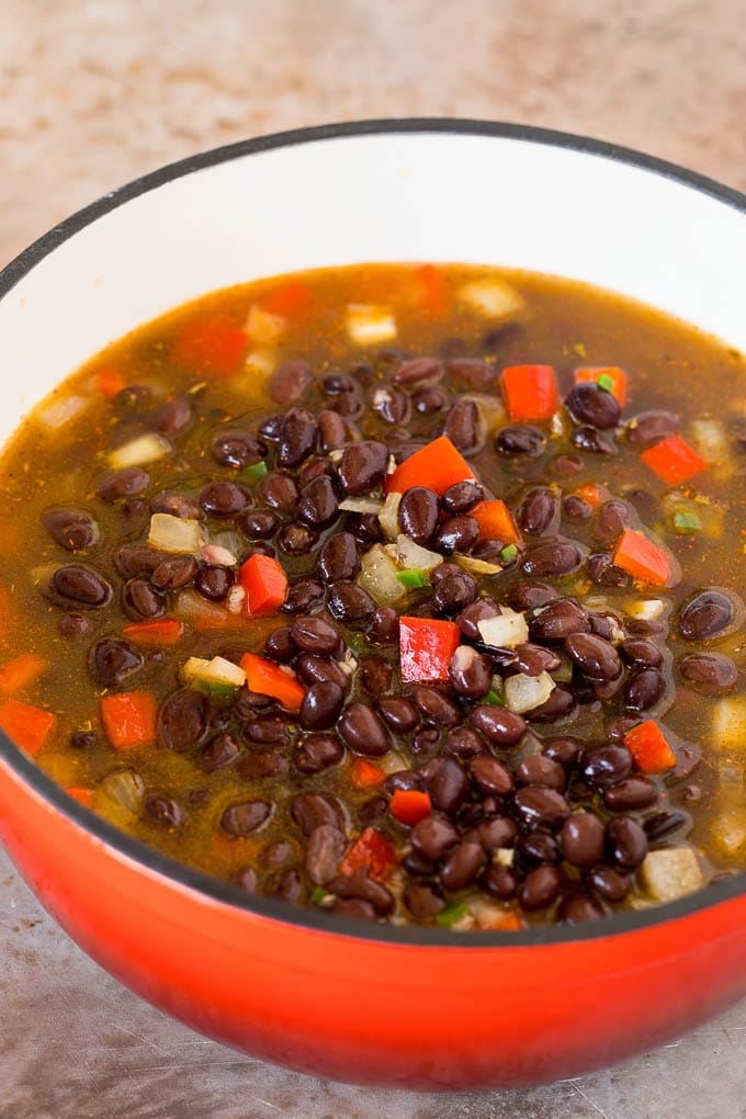 A pot of black beans, broth and vegetables.