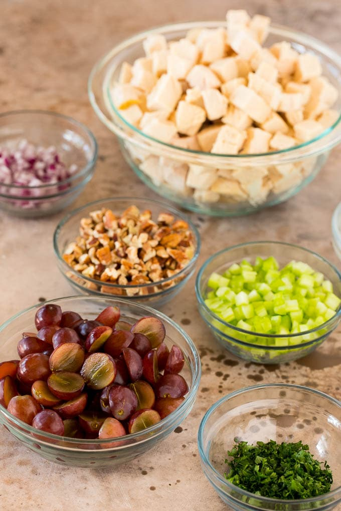 Bowls of diced chicken, celery, pecans, grapes, red onions and parsley.