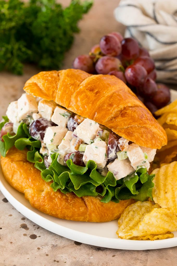 Chicken salad with grapes served on a croissant with chips.