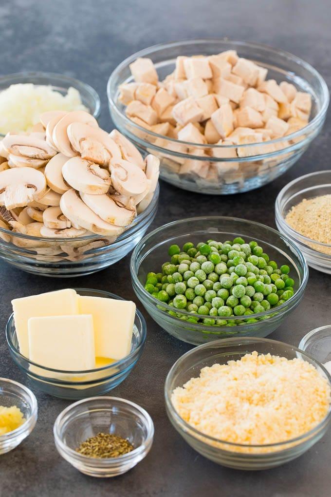 Ingredients in bowls including chicken, peas, mushrooms, cheese and seasonings.