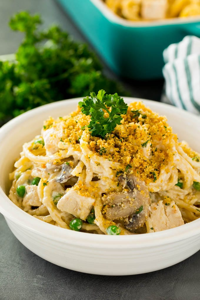 A bowl of chicken tetrazzini topped with breadcrumbs and parsley.