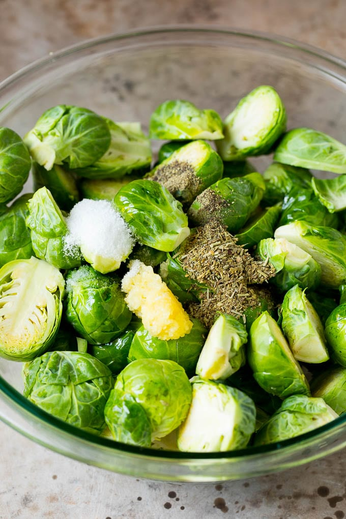 A bowl of Brussels sprouts with garlic, herbs, olive oil and spices.