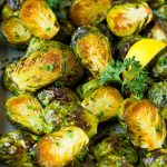 Crispy Brussels sprouts garnished with lemon slices and parsley.