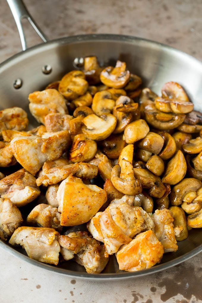 Cooked chicken and sauteed mushrooms together in a pan.