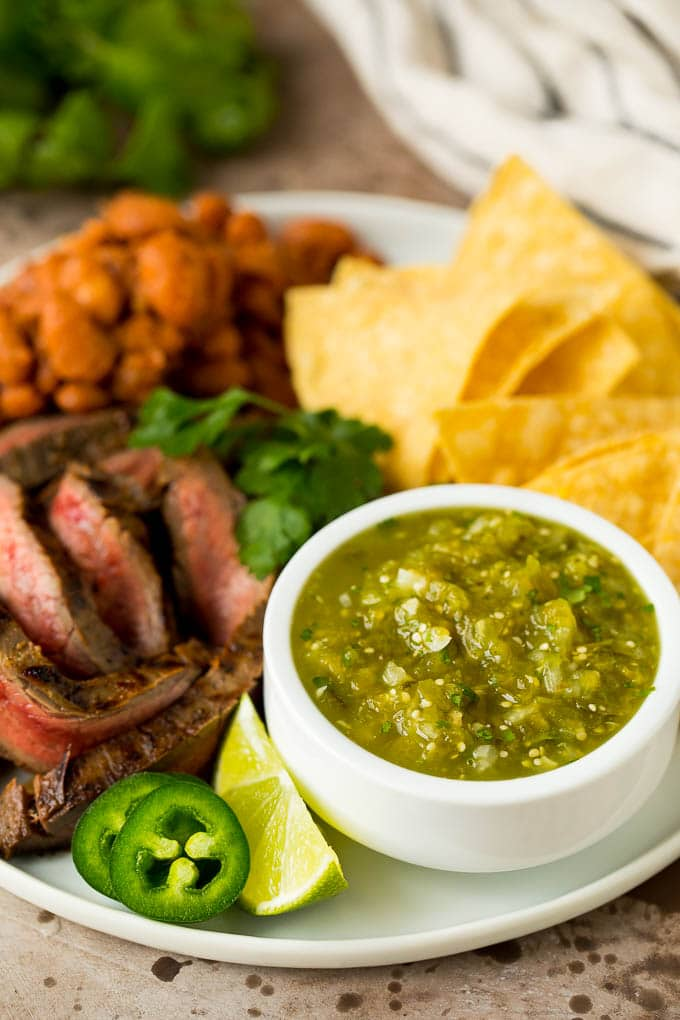 Salsa verde served with carne asada, beans and tortillas.