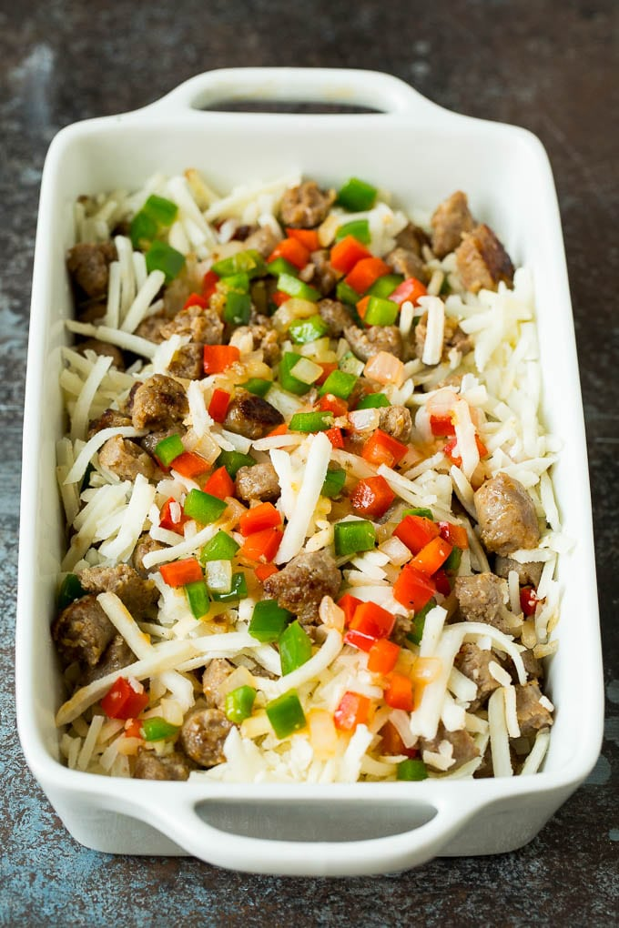 Hash browns, sausage and peppers in a baking dish.