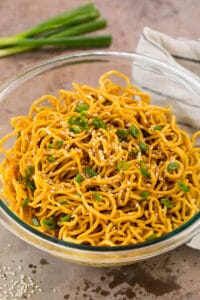 A bowl of sesame noodles garnished with sesame seeds and green onions.