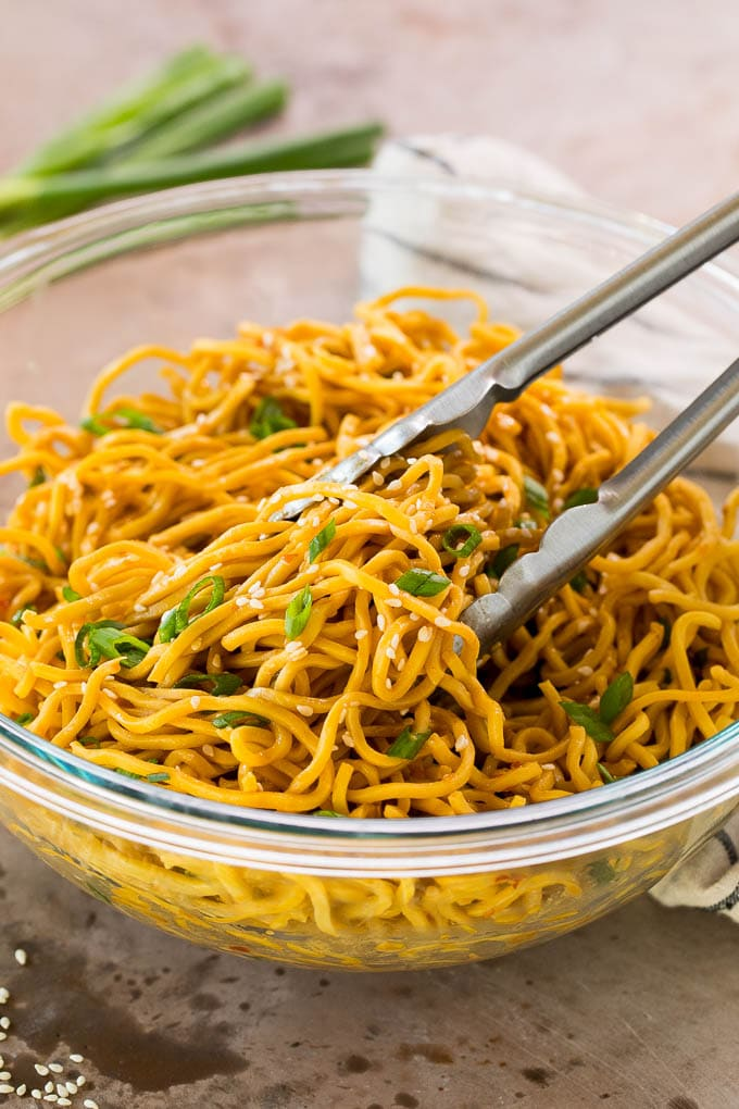 Tongs serving up a portion of Asian sesame noodles.