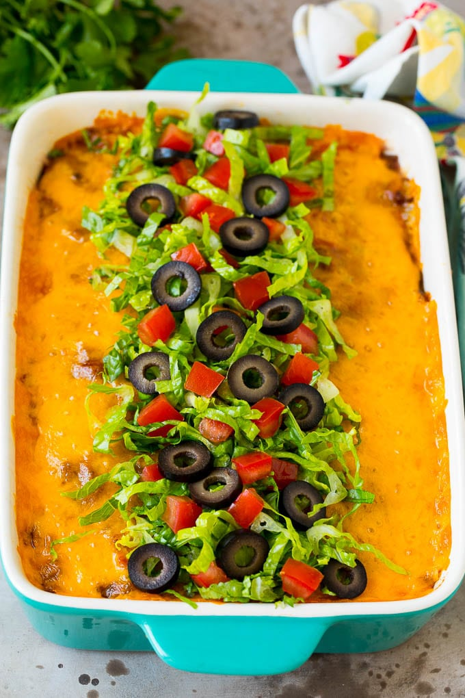 Taco bake topped with melted cheese, lettuce, tomatoes and olives.