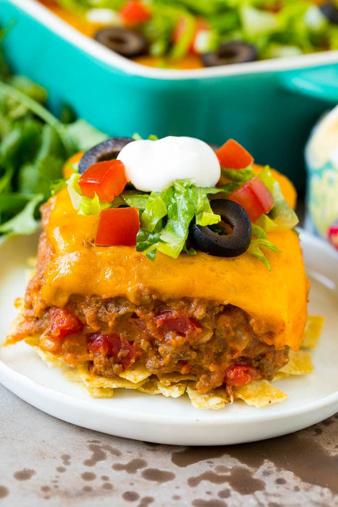 A slice of taco bake with a crust of tortilla chips and a filling of beef and beans.