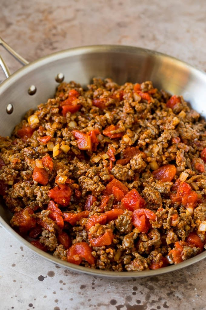 Ground beef, tomatoes and seasoning in a pan.