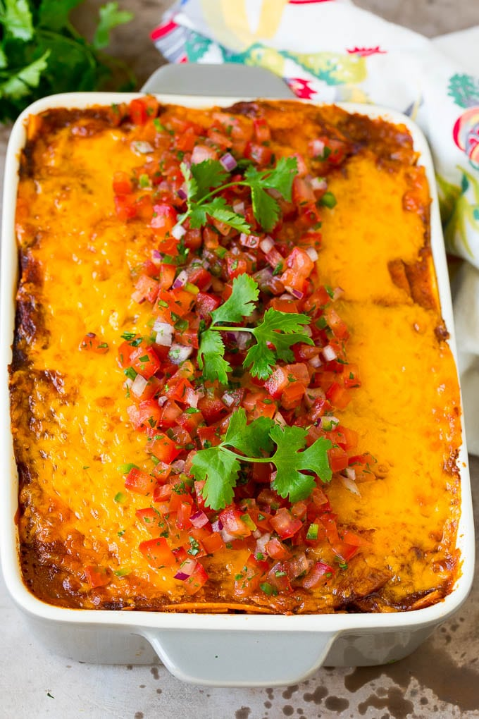 A pan of taco lasagna topped with fresh salsa and cilantro.