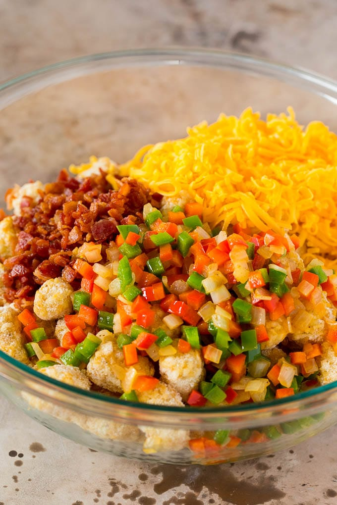 A bowl of frozen tater tots, vegetables, bacon and shredded cheese.