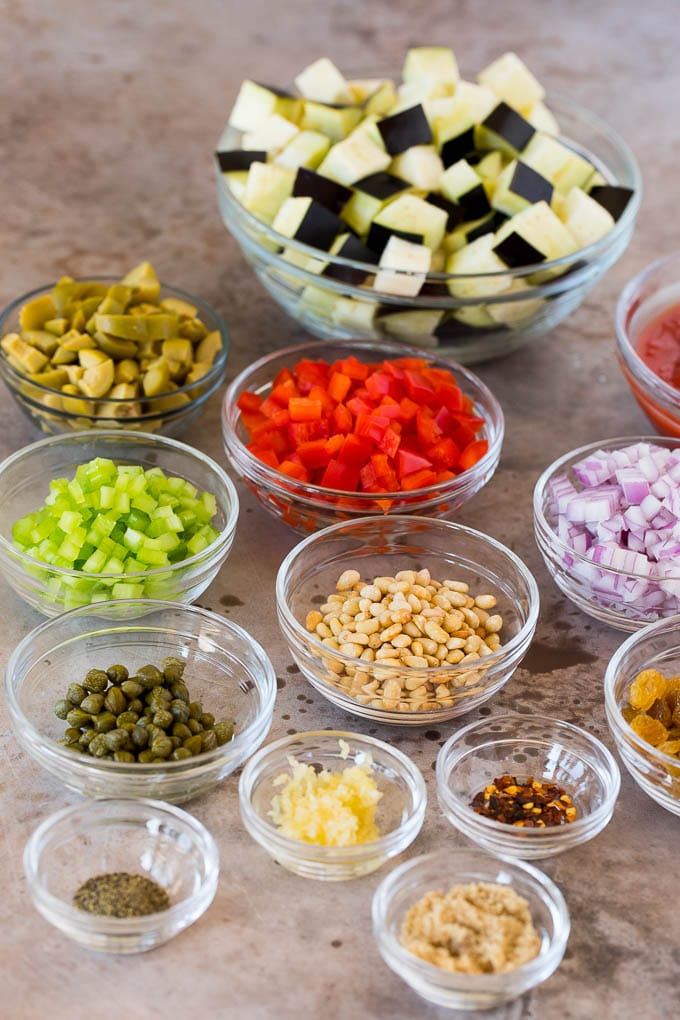 Bowls of ingredients including diced vegetables, olives, raisins and seasonings.