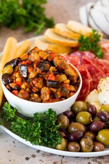 A bowl of eggplant caponata served with olives, cured meats and bread.
