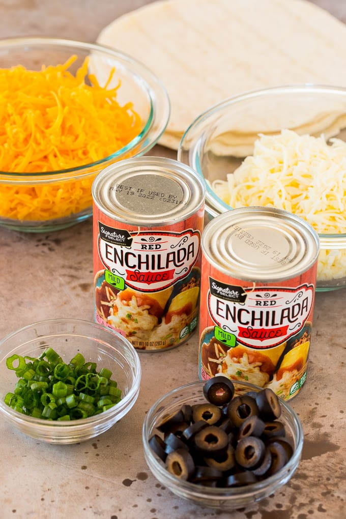 Cans of sauce and bowls of shredded cheese, green onions and olives.