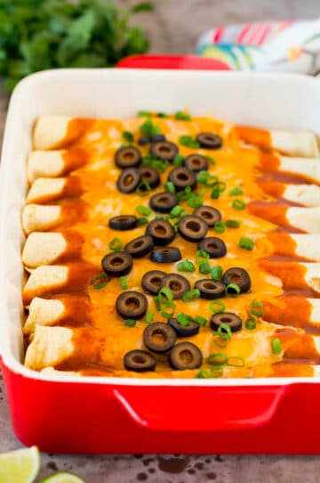 A dish of cheese enchiladas topped with olives and green onions.