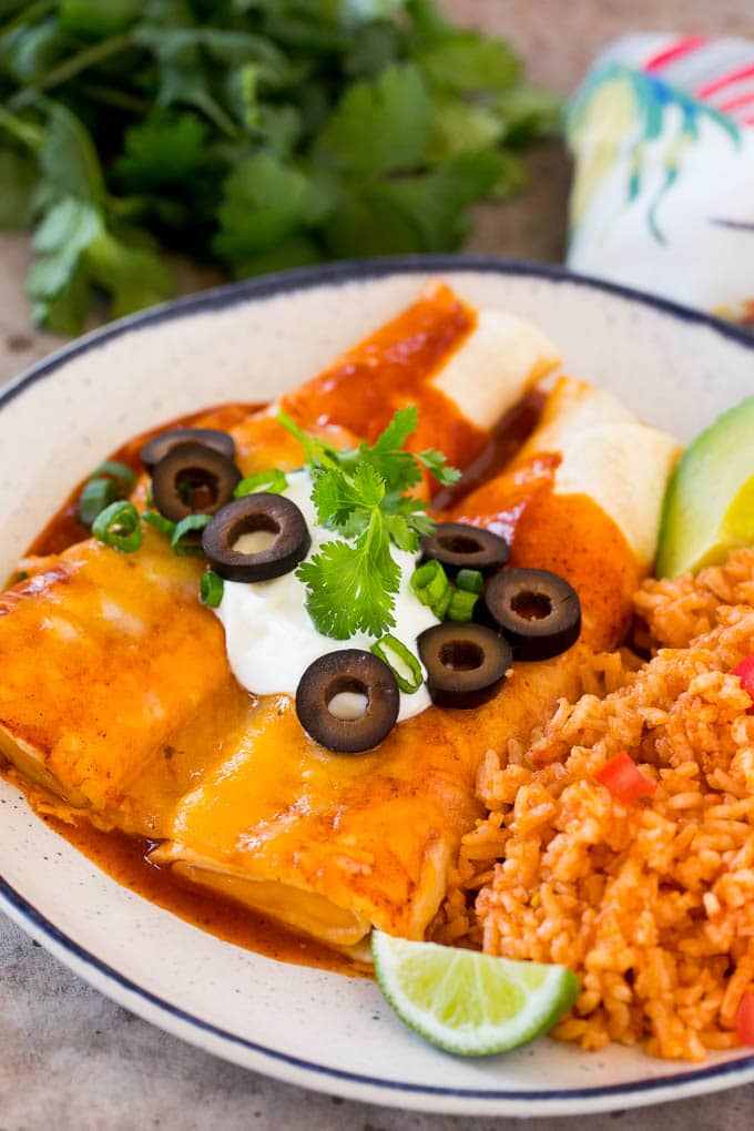 A plate of cheese enchiladas served with Mexican rice.