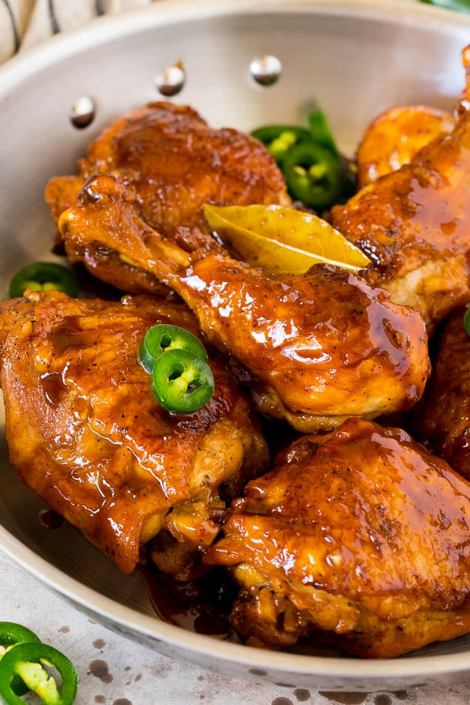 A pan of chicken adobo garnished with sliced jalapeno.