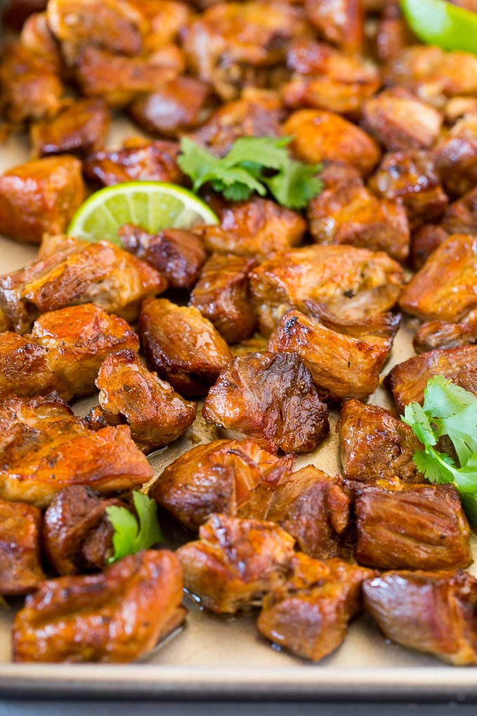 A sheet pan of Instant Pot carnitas garnished with lime and cilantro.