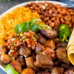 A plate of Instant Pot carnitas with rice, beans, salsa and tortillas.