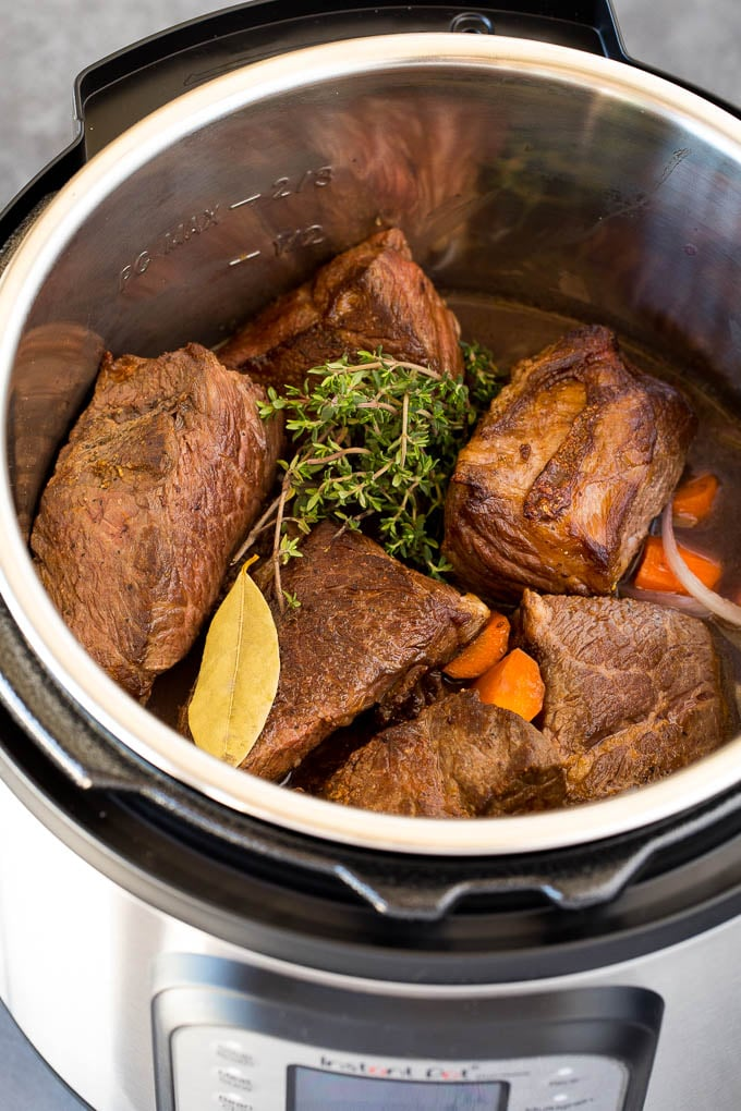 A pressure cooker with short ribs, herbs, vegetables and beef broth.